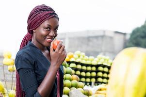 smiling young woman holding a tomato. photo