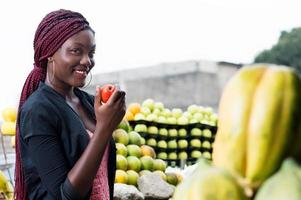 smiling young woman shows the chosen food. photo