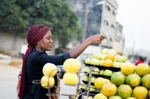 young woman paying fruits at street market. photo