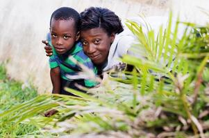 young woman hidden behind a flower with her child photo