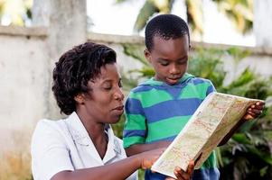 young woman reading a map with her child. photo