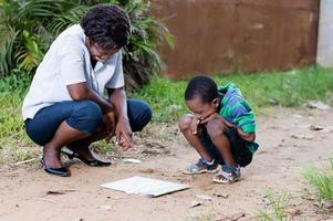 young woman reading a map with her child photo