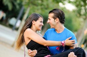 Love couple embracing outdoor in park looking happy photo