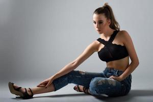 Young woman wearing black bra and blue jeans sitting on floor. Studio shot. photo