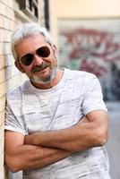 Mature man smiling with aviator sunglasses in urban background photo