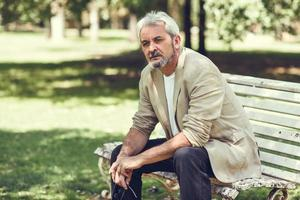 Pensive mature man sitting on bench in an urban park. photo