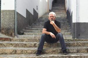 Mature man with white hair sitting on urban steps photo
