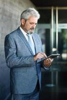 Senior businessman with tablet computer outside of modern office building. photo