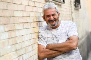 Mature man smiling looking at camera in urban background photo