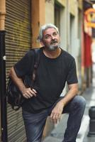 Mature tourist man with travel backpack in urban background. photo