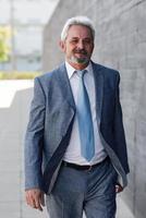Senior businessman walking outside of modern office building. photo