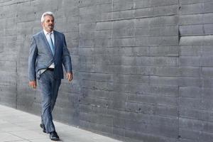 Serious senior businessman walking outside of modern office building. photo