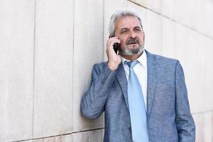 Senior businessman with smartphone outside of modern office building. photo