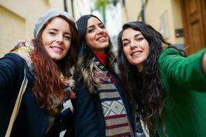 Group of three happy woman walking together outdoors photo