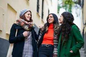 Multiethnic group of three happy woman walking together outdoors photo