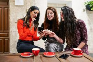 Group of three happy friends drinking coffee in a cafe bar. photo