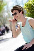 Attractive young man wearing hat talking on the mobile phone photo