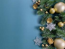 adornos navideños, hojas de pino, bolas doradas, copos de nieve, bayas doradas sobre fondo azul foto