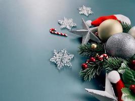 adornos navideños, hojas de pino, bolas de oro, copos de nieve, frutos rojos sobre fondo azul foto