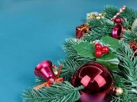 adornos navideños, hojas de pino, bolas doradas, copos de nieve, frutos rojos y frutos dorados sobre fondo azul foto