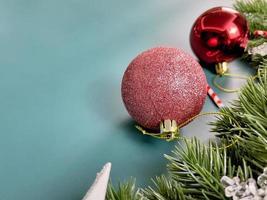 adornos navideños, hojas de pino, bolas rojas, copos de nieve, frutos rojos sobre fondo azul foto