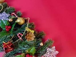 adornos navideños, hojas de pino, bolas doradas, copos de nieve, bayas doradas y frutos rojos sobre fondo rojo foto