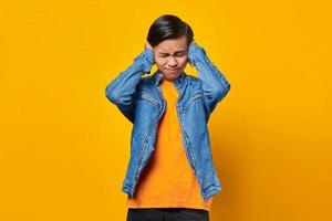 Portrait of angry Asian man covering his ears with hands photo