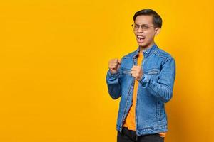 Portrait of angry young asian man showing boxer gesture on yellow background photo
