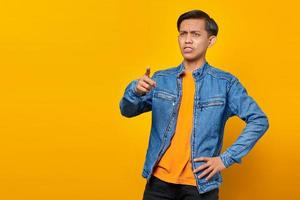 Portrait of angry Asian young man pointing finger at camera with open mouth photo