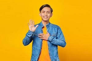 Asian young man smiling and greeting isolated on yellow background photo