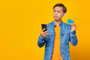 Shocked asian man holding mobile phone and showing credit card over yellow background photo