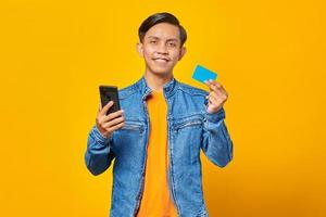 Portrait of smiling asian man using credit card to pay with mobile phone photo