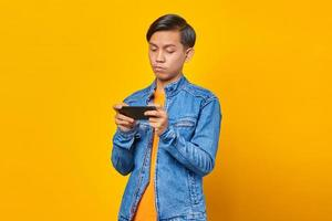 asian man using mobile phone playing game with angry face over yellow background photo