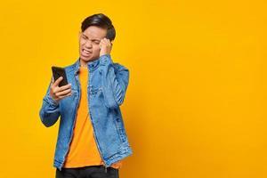 Conmocionado joven asiático mirando el mensaje en el teléfono inteligente foto