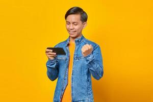 Portrait of enthusiastic asian man playing game on mobile phone and celebrating victory photo
