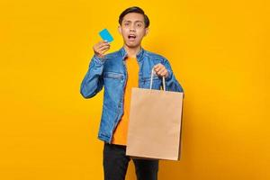 Portrait of shocked asian man holding credit card and shopping bag over yellow background photo