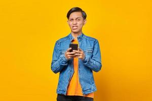 portrait of angry young man looking at camera and holding smartphone photo