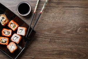 Sushi roll with chopsticks photo
