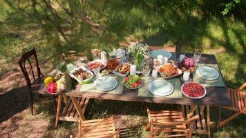 vue de dessus personne n'a tourné des images d'une table à manger en bois préparée pour la fête d'été dans un parc verdoyant sous les arbres video