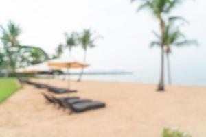 Silla de playa de desenfoque abstracto en la playa con mar océano de fondo - concepto de viajes y vacaciones foto