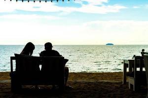 Amor de pareja de silueta con vista al mar - filtro de efecto vintage foto