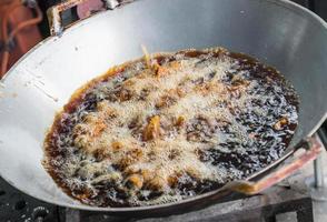 Pollo frito en sartén con aceite hirviendo foto