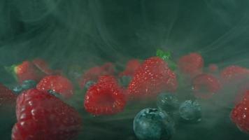 Macro studio shot of fresh natural mix of juicy summer berries lying in transparent smoke on dark background video