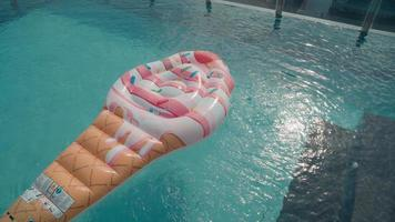 High-angle shot of transparent shiny pool water with inflatable lounge in shape of ice cream inside video