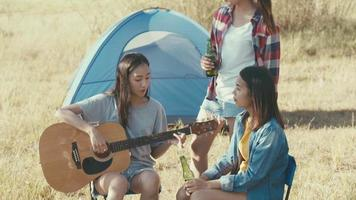Asian women camping in nature playing guitar and drinking beer video