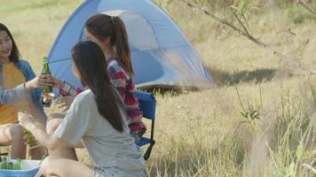 Asian woman happy with friends camping in nature having fun together drinking beer and clinking glasses. video