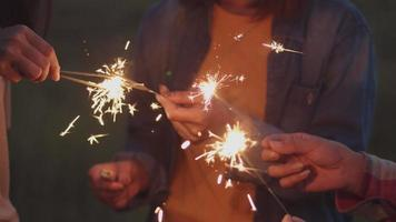 Asian woman holding sparklers celebrating new Year with friends video