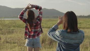 Young women taking pictures on the smartphone during sunset video