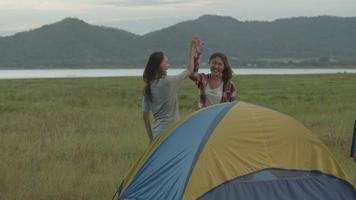 femmes asiatiques campant au coucher du soleil, s'amusant ensemble lors d'un voyage d'été video