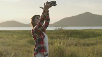 Asian woman selfie video chat with her friends on the smartphone while sunset.